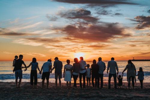 Foto. Familien am Strand am Meer bei Sonnenuntergang